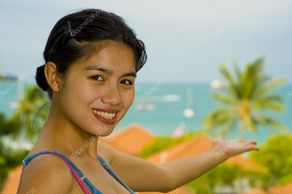 Beautiful asian woman pointing to the sea — Stock Photo #2542539