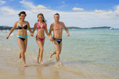 Family running at the beach — Stock Photo