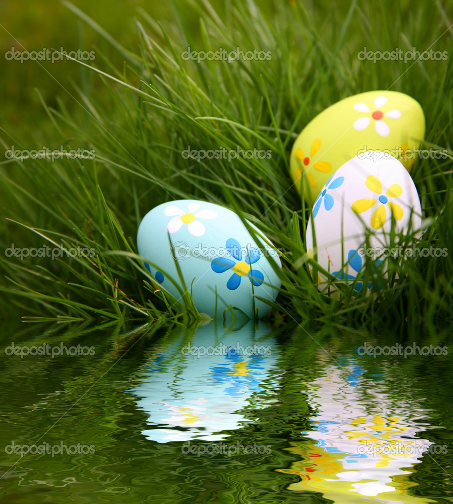 Painted Colorful Easter Eggs in Grass Reflecting in Water — Stock Photo #2553525