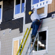 Man Hanging Siding - Construction - Stock Photo