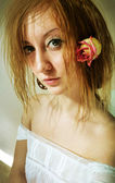 Beautiful girl with rose in her hair — Stock Photo