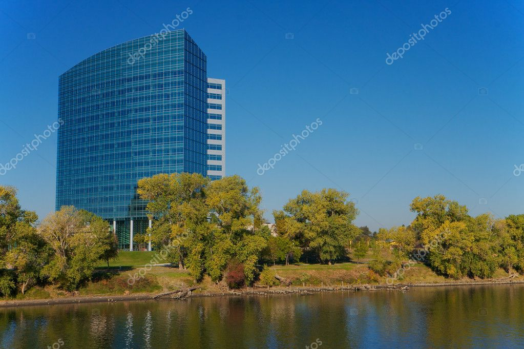 Modern building on river with blue sky and green trees  Stock Photo #2536885