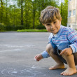 Stock Photo: Boy draws with chalk on asphalt