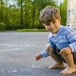 The boy draws with chalk on asphalt — Stock Photo