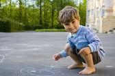 The boy draws with chalk on asphalt — Stock Photo