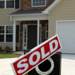 Foto de Stock  : SOLD Sign in Front of Beautiful New Home