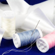 Thread with needle and ribbon - Stock Photo