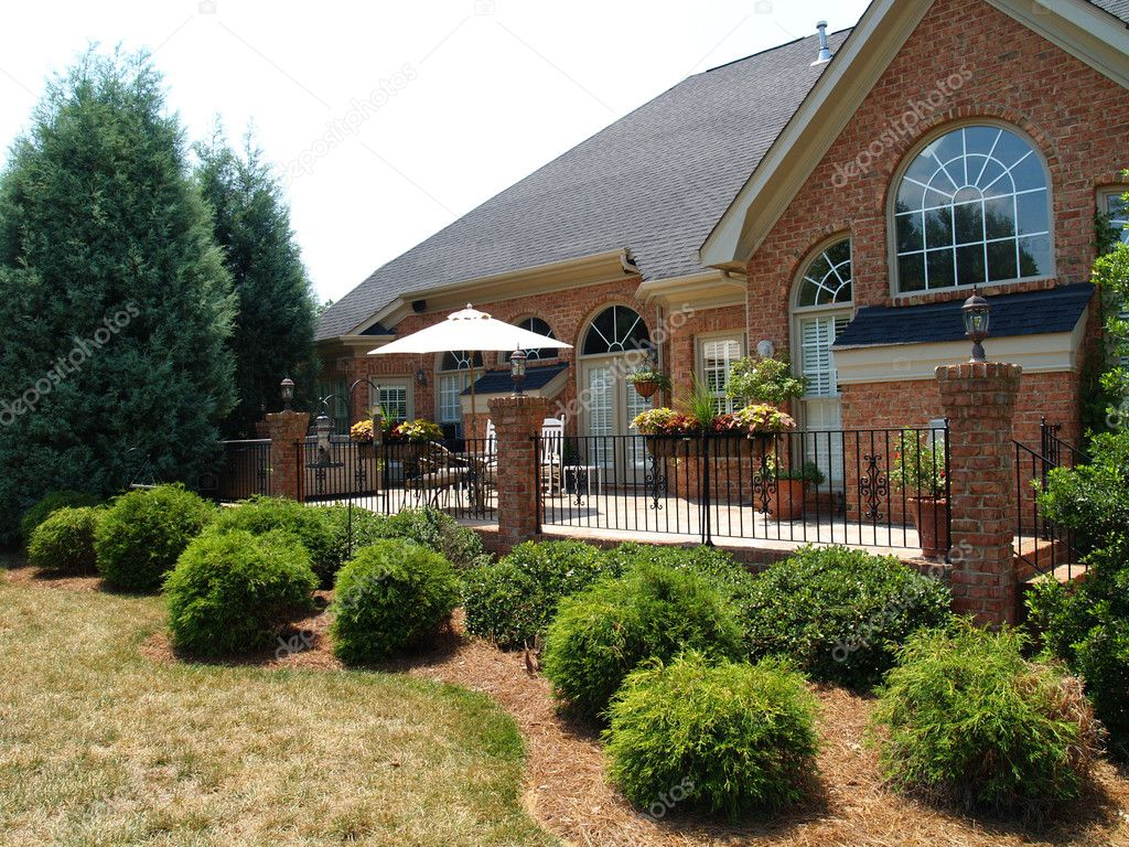 Large brick patio with an iron railing on the back of an expensive home with arched windows. Well-kept planters and a covered table decorate the exterior room. — Photo #2559021