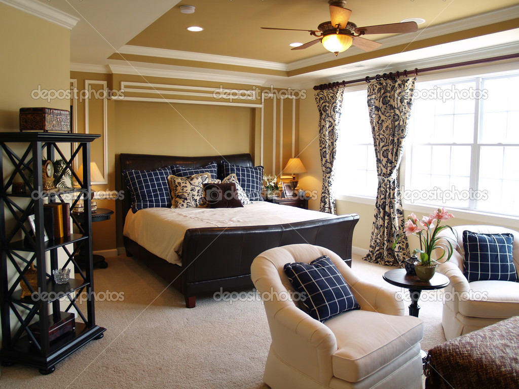 Nicely decorated master bedroom in a newly built luxury home. There is a black leather sleigh bed, dark furniture, light streaming through the windows, and a li — Stock Photo #2559186