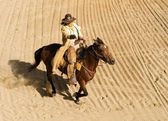 Cowboy riding into town at full gallop — Stock Photo