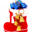 Red Christmas boot with gifts and bells — Stock fotografie