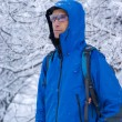 A backpacker man in winter forest — Stock Photo