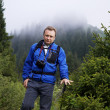 Backpacker man in mountain pine forest — Stock Photo