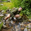 Mountain Biker drinking from a stream — Stock Photo