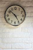 Clock on white brick wall — Stock Photo