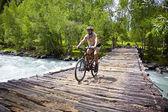 Motociclista da montanha continua a velha ponte de madeira — Fotografia Stock