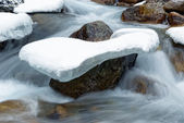 Stone in the ice and stream — Stock Photo