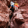 Couple climbing in red rocks — Stock Photo