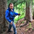 Backpacker man in pine forest — Stock Photo