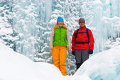 Couple backpackers and ice waterfall — Stock Photo