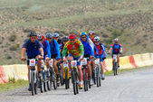 Mountain bikers group racing on road in desert — Stock Photo