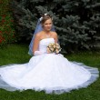 Bride blonde sits on grass — Stock Photo