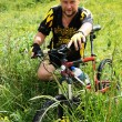 Mountain biker waits on green field - Zdjęcie stockowe