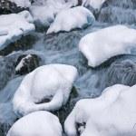 Winter mountain creek cascades during snowfall — Stock Photo