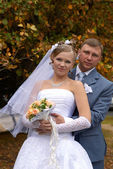 Newly-married couple in autumn park — Stock Photo