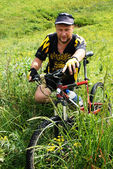 Mountain biker waits on green field — Stock Photo