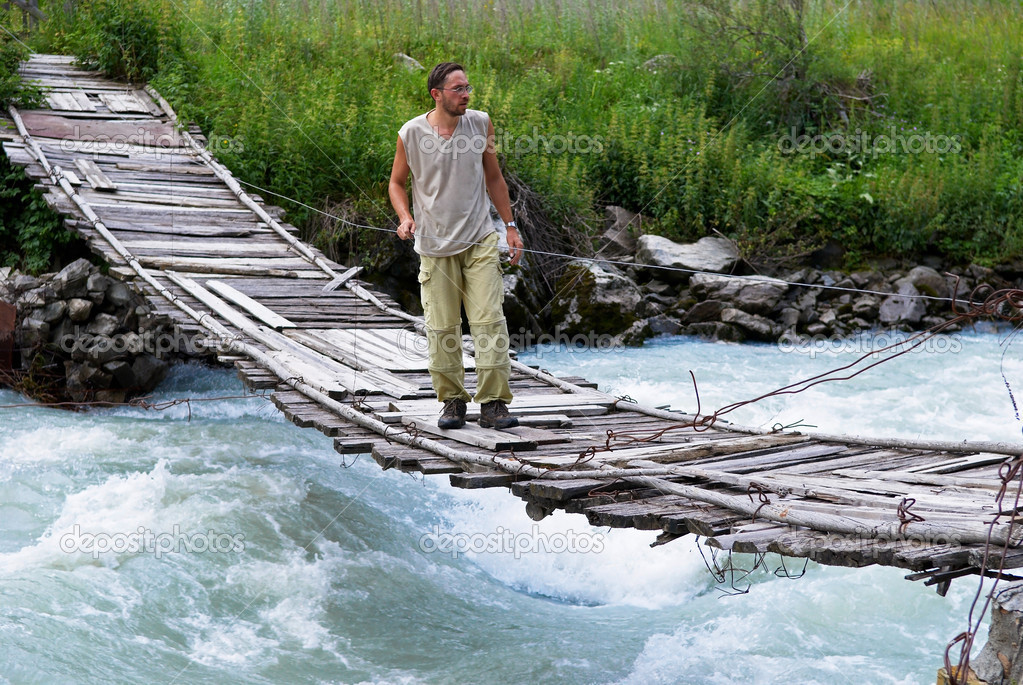 Man on old suspension bridge — Stock Photo #2682475