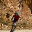Mountain biker racing near rocks — Stock Photo
