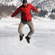 Main in red jumping on winter mountain lake — Stock Photo