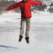 Main in red jumping on winter mountain lake — Stock Photo #2693517