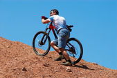 Mountain biker uphill for download — Stockfoto