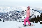 Merry snowboard girl in pink cloth before downhi — Stock Photo