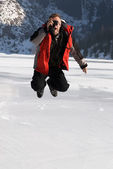 Main in red with photo jumping on winter mountai — Stockfoto