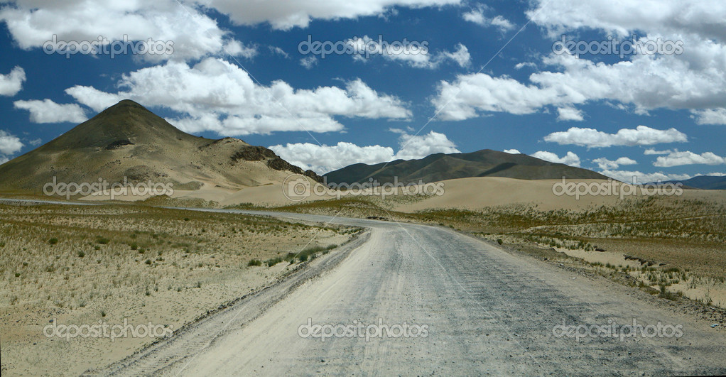 The wide road conducting to a foot of mountains in the deserted lands — Stock Photo #2539314