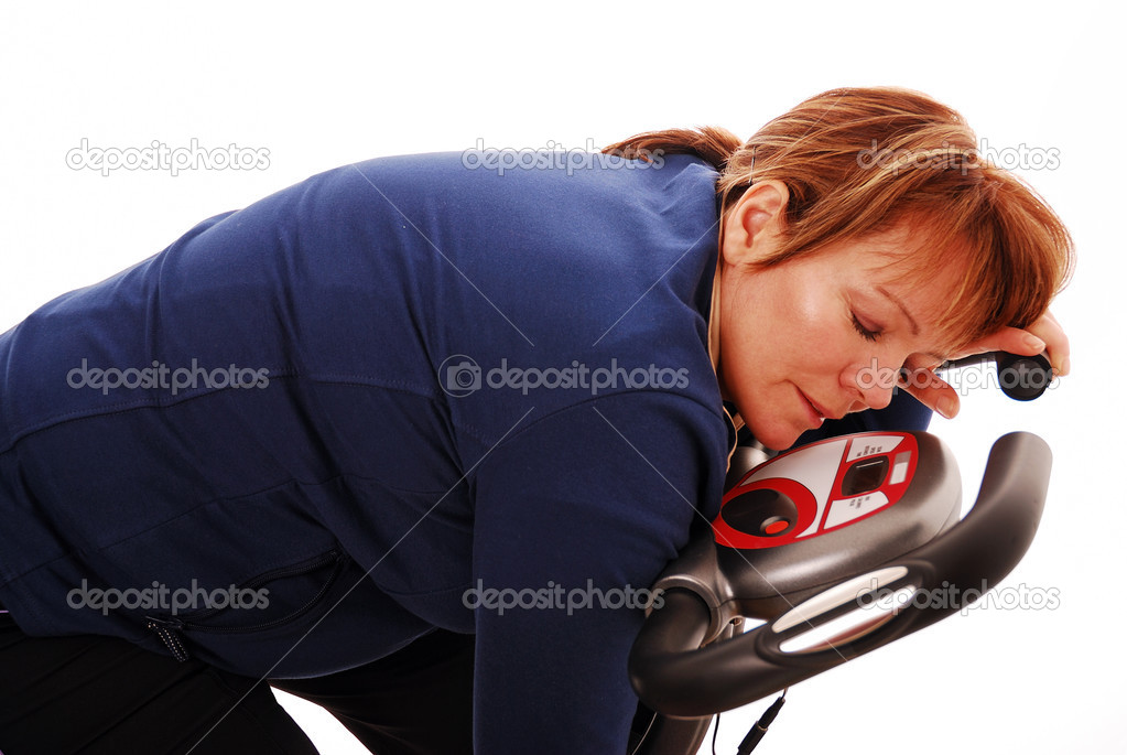 Woman asleep on exercise bike exhausted after workout — Stock Photo #2539875