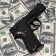 Black gun on US dollars background — Stock Photo