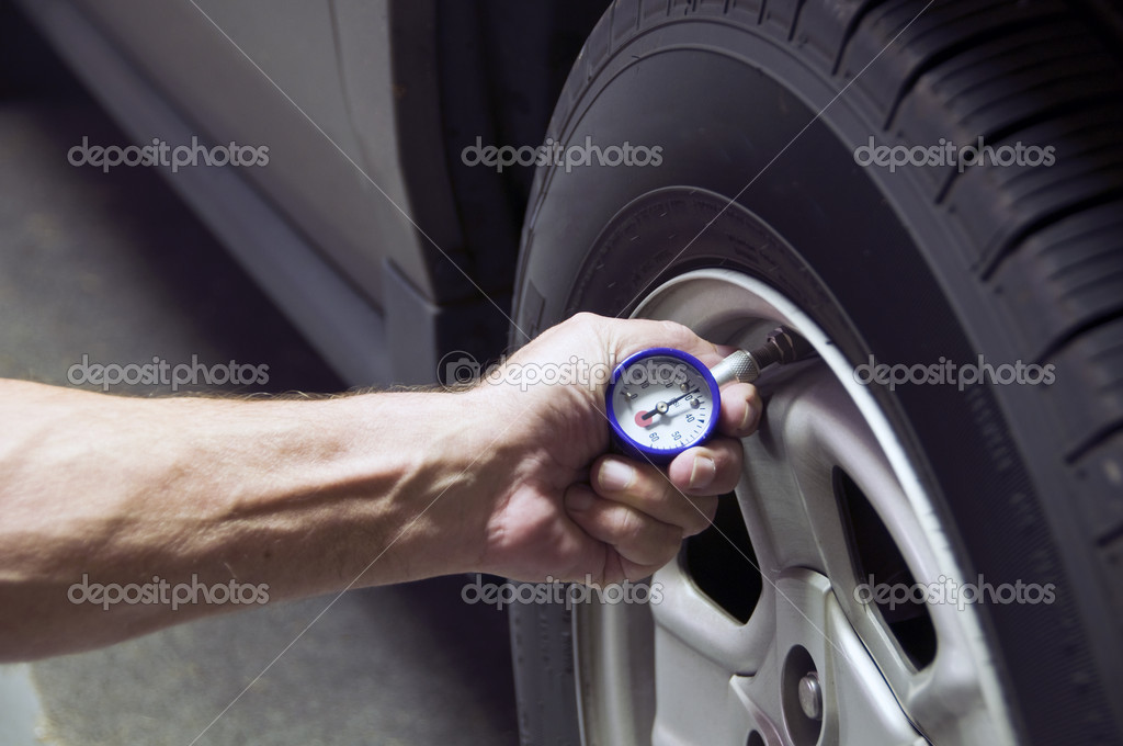 Mechanic checking tire pressure for increased gas mileage — Zdjęcie stockowe #2641694