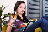 Cute Girl Drinking while Reading a Book — Stockfoto