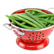 Washed string beans in red colander. - Stock Photo