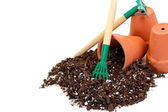 Clay flower pots, soil and a rake — Stock Photo