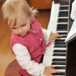 Stock Photo: Girl plays piano