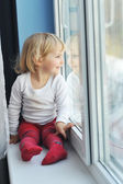 Girl sits at window — Stock Photo