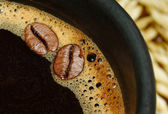 Black coffee cup and coffee beans — Stock Photo