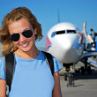 Young woman in front of the airplane — Stock Photo