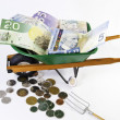 Canadian dollars in wheel barrel - Stock Photo
