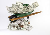 Wheel barrel filled with cash — Stock Photo